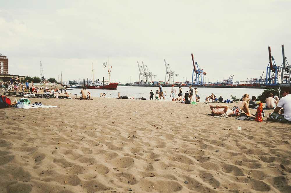 Badende Mesnchen an einem sandigen Strand der Elbe in Deutschland