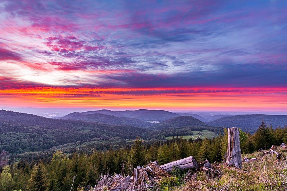 Auf dem vom Aussichtspunkt aus aufgenommenen Bild ist ein Sonnenuntergang hinter dem Schwarzwald mit atemberaubenden Abendrot zu sehen.