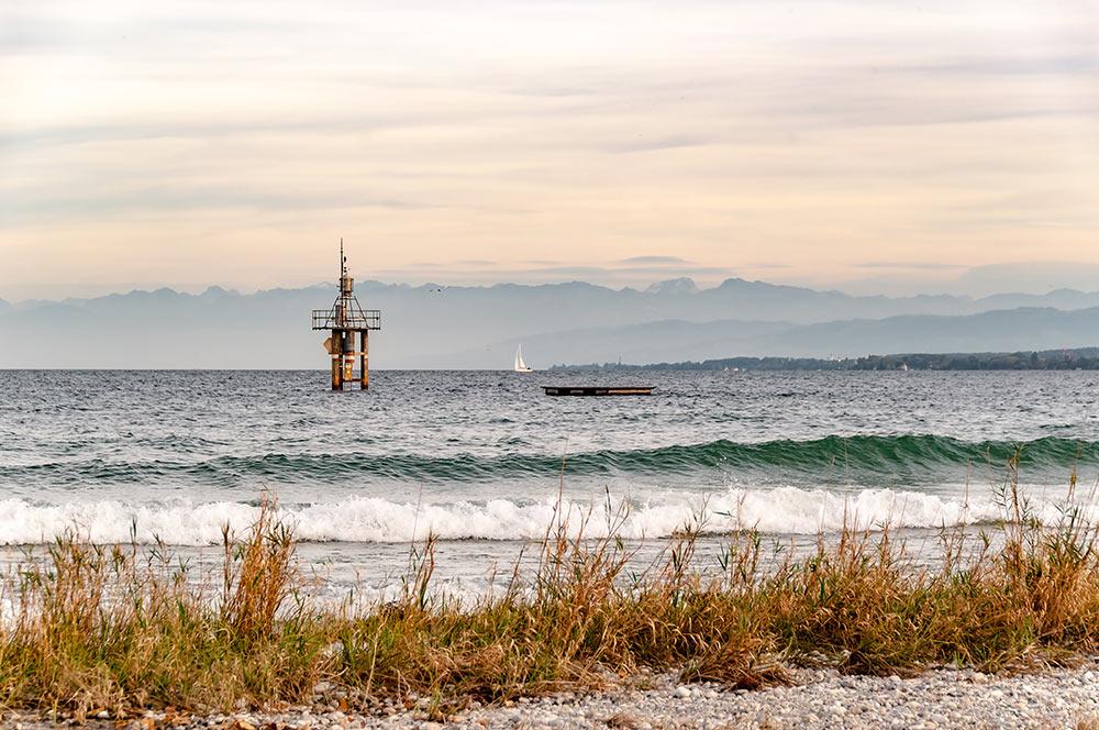 Das Bild zeigt den Bodensee mit allen Ländern, die an ihn grenzen: Im Vordergrund ist ein Strand zu sehen, der in Deutschland liegt, das Ufer rechts liegt in der Schweiz. Und die Berge im Hintergrund gehören zu Österreich.