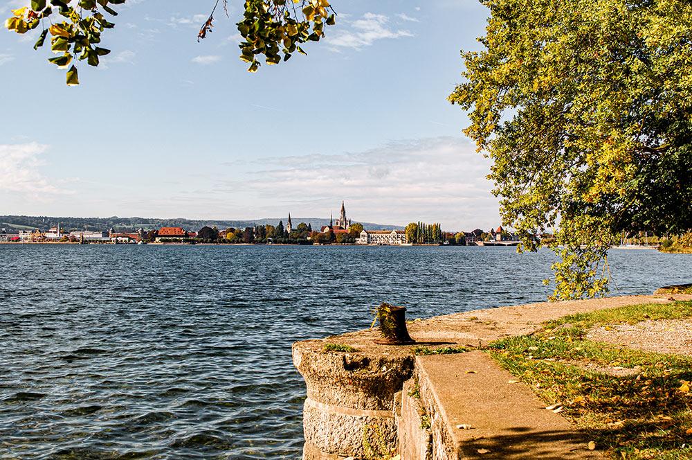 Das Bild zeigt das Land Deutschland, wie es an den Bodensee grenzt. Die Stadt im Hintergrund ist Konstanz.