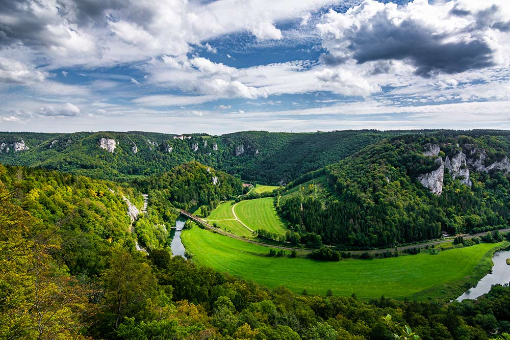 Auf dem Bild ist die Landschaft im oberen Donautal zu sehen mit einer der Donauschleifen. Auf einem der Felsen steht die Burg Wildenstein.