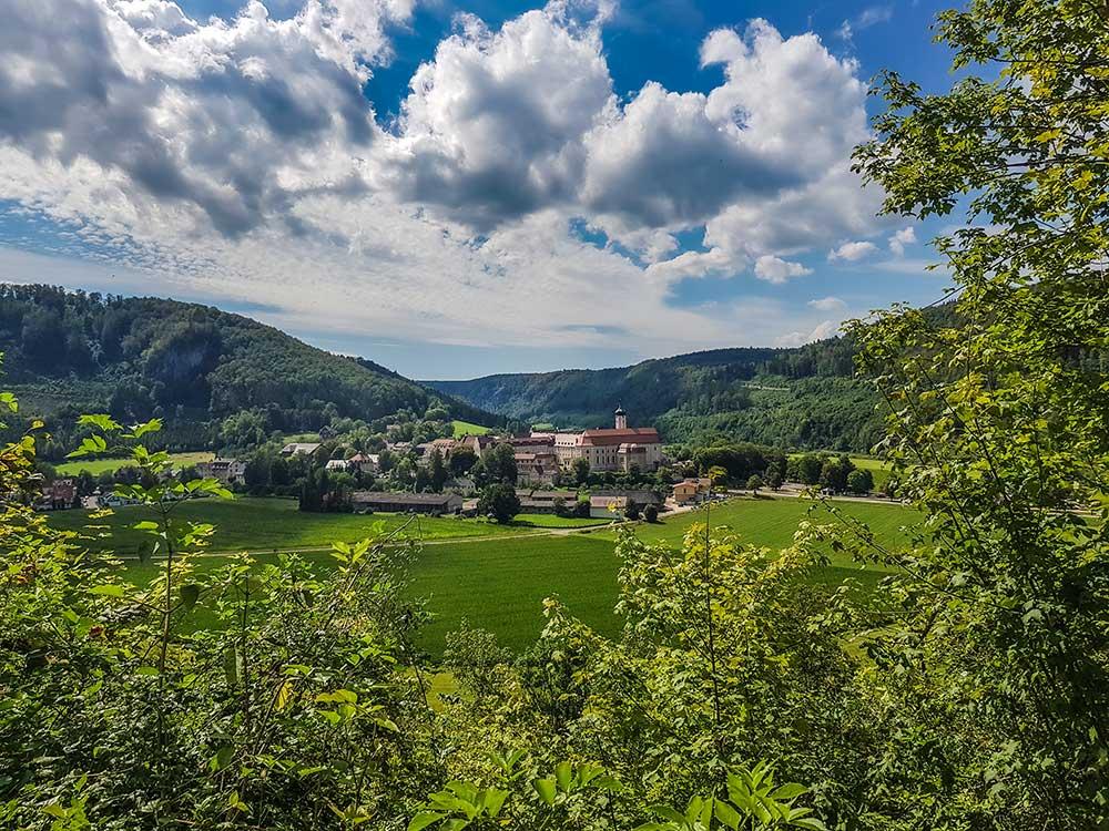 Auf diesem Bild ist Beuron im oberen Donautal mit der riesigen Klosteranlage zu sehen. Ein Wanderweg führt am Hang unter den Felsen entlang und bietet immer wieder schöne Blicke in die Landschaft.