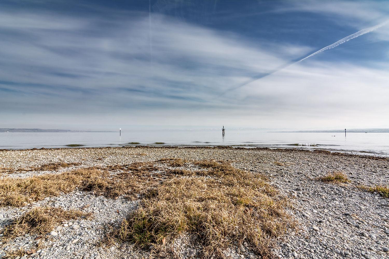 Das Bild zeigt den Bodensee von einem Strand aus