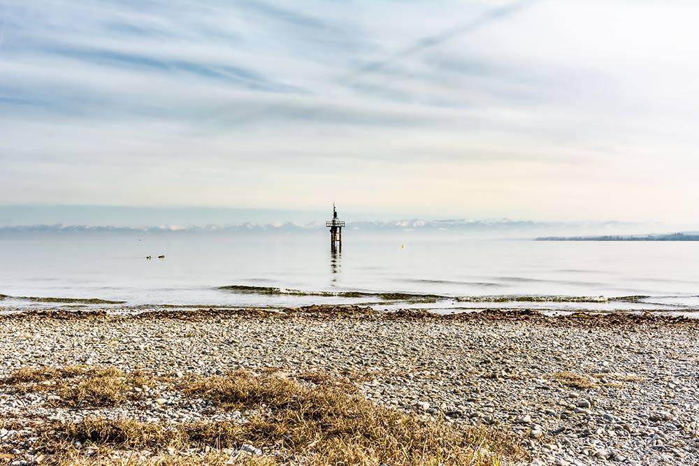 Hier am Bodensee kannst du zwei der Nachbarländer von Deutschland auf einmal entdecken. Im Hintergrund links sind die Berge von Österreich zu sehen, das Ufer rechts gehört zur Schweiz. Im Vordergrund ist Deutschland.